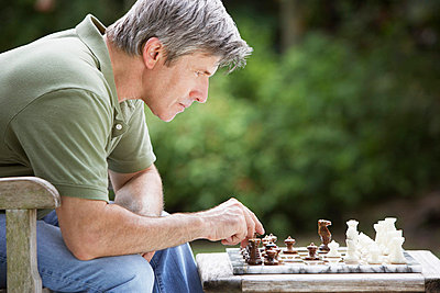 Man outdoors playing chess - p6418286f by Tom Merton