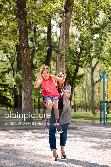 Girl being pushed by mother on swing in park - p1192m2129916 by Hero Images