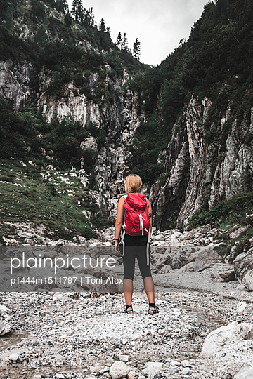 Woman hiking between the mountains - p1444m1511797 by Toni Alex