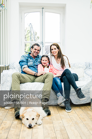 Portrait of happy family with dog in living room - p300m1587931 von Robijn Page