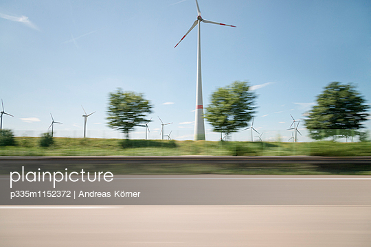Wind farm along the highway blurred view - p335m1152372 by Andreas Körner