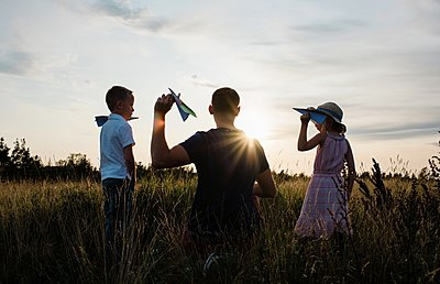 father playing planes with son and daughter in a meadow at sunset - p1166m2137840 by Cavan Images