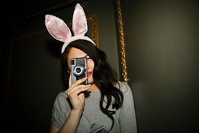 Portrait confident, playful female millennial with retro camera wearing costume rabbit ears - p1192m1583669 by Hero Images