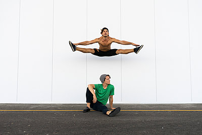 Two acrobats doing tricks together, jumping mid-air - p300m2012362 von VITTA GALLERY