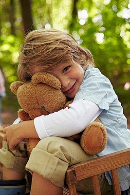 Portrait of boy hugging teddy bear in forest - p300m2180038 by Stefanie Aumiller