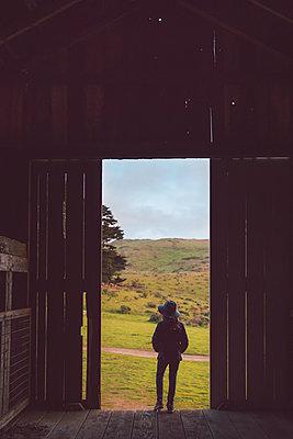 Girl in a barn, rear view, California - p756m2211768 by Bénédicte Lassalle