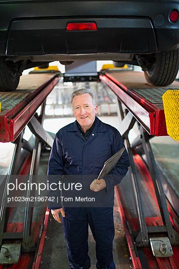 Portrait confident male mechanic under car in auto repair shop - p1023m2196742 by Tom Merton