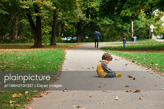 A small boy sits on a leaf-strewn path as his family walks on - p1166m2131337 by Cavan Images