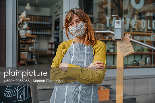 Mature store owner with arms crossed standing against organic store during pandemic - p300m2256235 by Mareen Fischinger