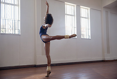Graceful young female dancer practicing in dance studio - p1023m2001429 by Sam Edwards
