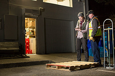 Workers using tablet computer while standing by warehouse at night - p1166m1417425 by Cavan Images