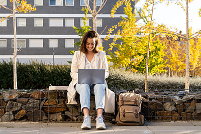 Smiling businesswoman using laptop while sitting on retaining wall in city - p300m2239929 by VITTA GALLERY
