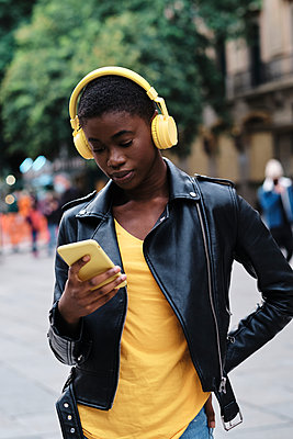 Young woman wearing headphones using smart phone while standing with hand on hip in city - p300m2250177 by Alvaro Gonzalez