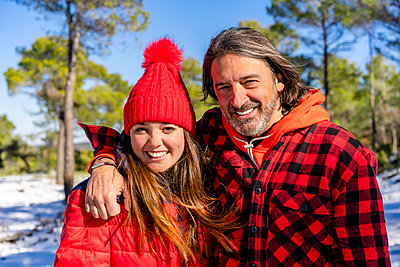 Father smiling while standing with arm around daughter in forest - p300m2250967 by Javier De La Torre Sebastian