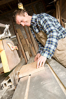 A carpenter sawing wood in a workshop - p3018713f by Adam Burn