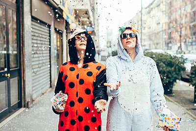Women wearing adult bodysuits throwing confetti in street - p429m2019187 by Eugenio Marongiu