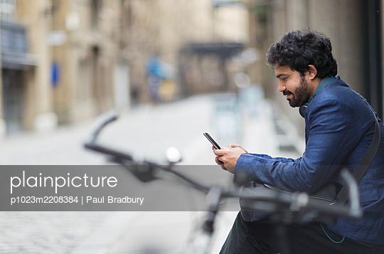 Businessman with bicycle using smart phone on city street - p1023m2208384 by Paul Bradbury