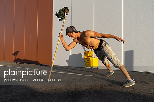 Acrobat playing with cleaning bucket and mop - p300m2012386 von VITTA GALLERY