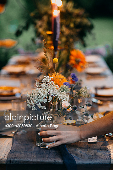 Hand placing flower vase on festive laid table with candles outdoors - p300m2059830 by Alberto Bogo