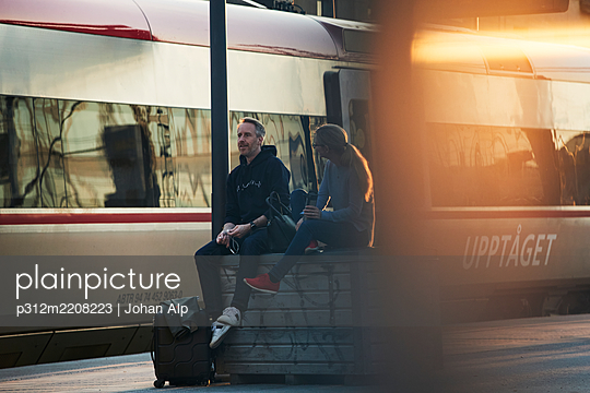 Couple waiting at train station platform - p312m2208223 by Johan Alp