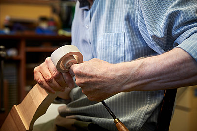 A violin maker using hand tools to smooth and finish a new wooden violin headstock, curled scroll of wood.  - p1100m1177899 by Mint Images
