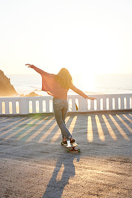 Female longboarder on boardwalk at sunset  - p1124m1503655 by Willing-Holtz