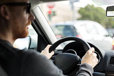 Mann fährt Auto im Stadtverkehr - p1396m1481163 von Hartmann + Beese