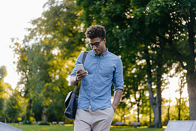 Young man looking at cell phone in park - p300m1535953 by Kniel Synnatzschke