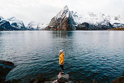 Happy tourist standing on a rock at Hamnoy, Lofoten, Norway - p300m2166508 by Daniel González