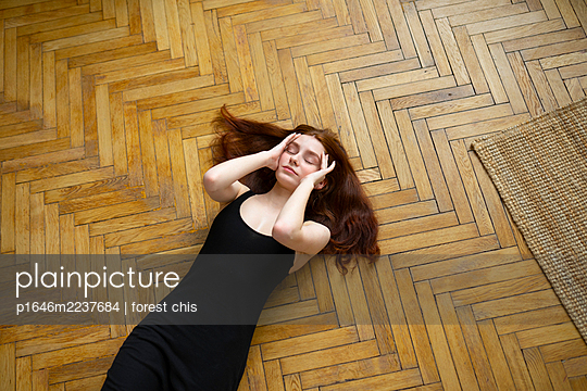 Young woman with brown hair lying on parquet floor - p1646m2237684 by Slava Chistyakov