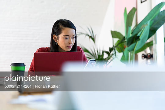 Woman using cell phone and laptop in office - p300m2114264 by Florian Küttler