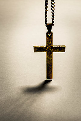 An old metal cross or crucifix hanging from a metal chain, a religious icon or symbol often used by the christian faith. - p1057m1572924 by Stephen Shepherd