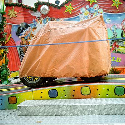 Karussellfahrzeug eines Kinderkarussells abgedeckt unter oranger Plane - p1180131 von Daniel Sadrowski