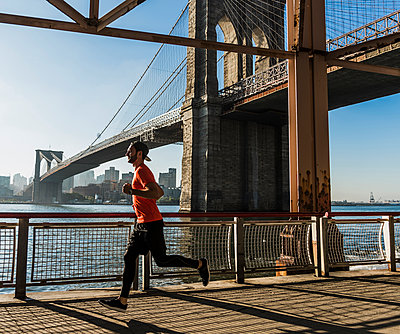 USA, New York City, man running at East River under Brooklyn Brige - p300m1191821 by Uwe Umstätter