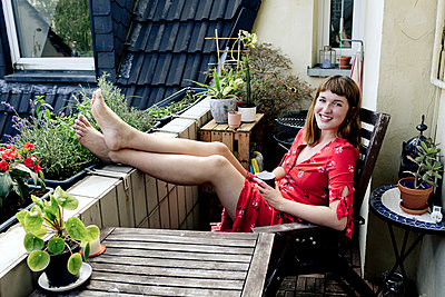 Portrait of smiling young woman relaxing with cup of coffee on balcony - p300m2131851 by FL photography