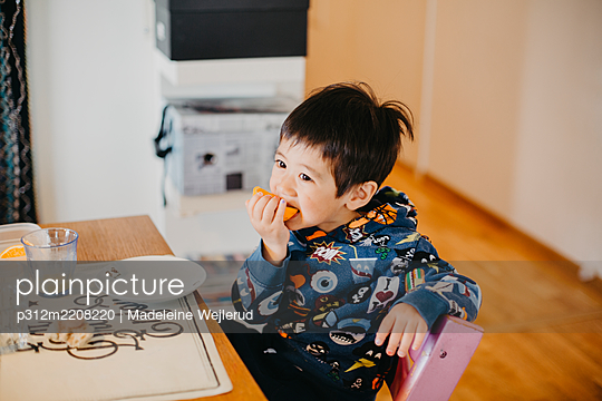 Boy at table eating fruit - p312m2208220 by Madeleine Wejlerud