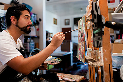 Side view of painter painting on canvas in art studio - p1166m1473620 by Cavan Images