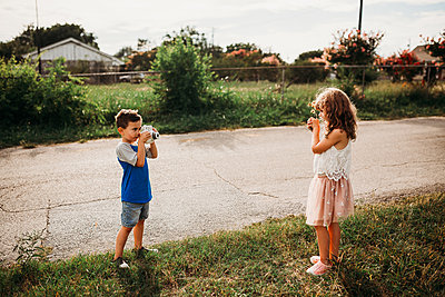 Brother taking photo of sister holding flowers outside at sunset - p1166m2201683 by Cavan Images