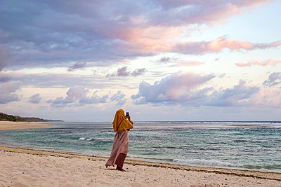 Woman photographing ocean coastline, Sumbawa, Indonesia - p1166m2202327 by Konstantin Trubavin