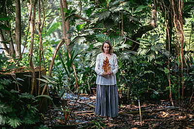 Woman standing in tropical forest  - p1414m1590574 by Dasha Pears