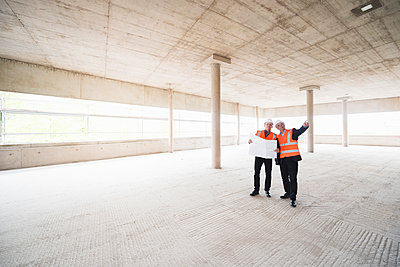 Two men with plan wearing safety vests talking in building under construction - p300m1460187 by Daniel Ingold