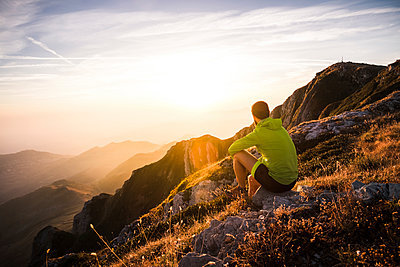 Italy, mountain running man sitting on rock looking at sunset - p300m1505174 by Simona Pilolla