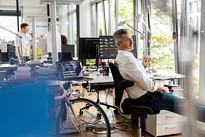 Businessman looking away while sitting on chair with colleagues in background at open plan office - p300m2257076 by Peter Scholl