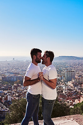 Gay men embracing while standing against cityscape during sunny day, Bunkers del Carmel, Barcelona, Spain - p300m2257326 by Veam
