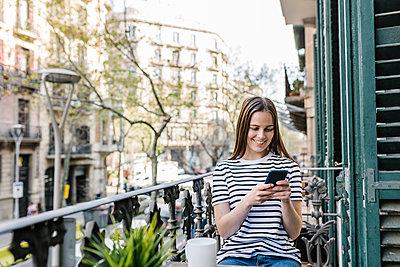 Happy woman using smart phone while sitting in balcony - p300m2282681 by Xavier Lorenzo