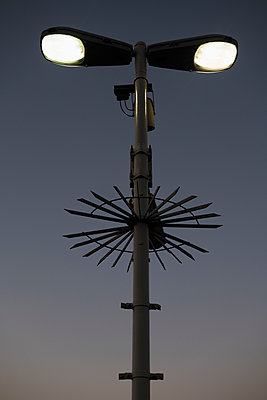 Low angle view of illuminated street light and surveillance cameras against sky - p301m1579746 by Michael Mann