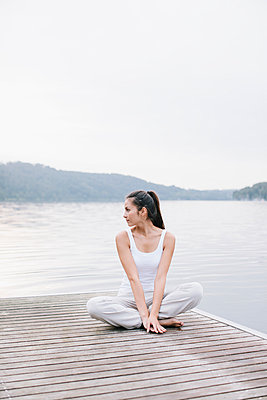 Yoga am See, Frau sitzt mit gekreuzten Beinen - p586m956102 von Kniel Synnatzschke
