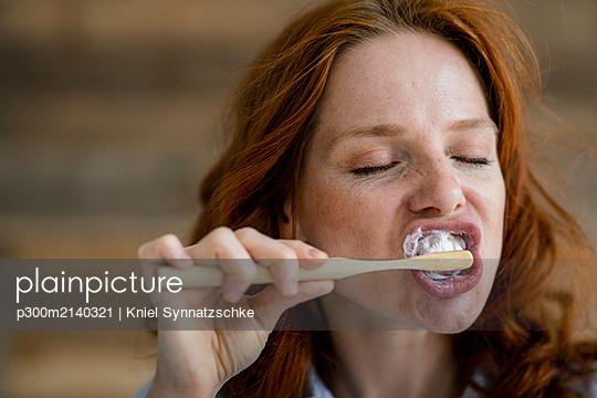 Portrait of redheaded woman brushing teeth - p300m2140321 by Kniel Synnatzschke