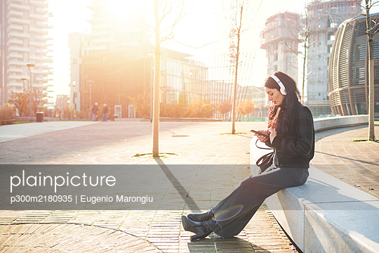Beautiful woman sitting on a bench and using smartphone, listening to music - p300m2180935 by Eugenio Marongiu