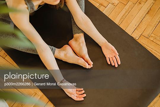Woman exercising yoga on mat at home - p300m2266286 by Gerard Moral Casanovas